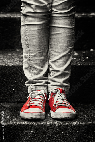 Obraz w ramie Little girl in red sneakers and jeans standing on the stairs
