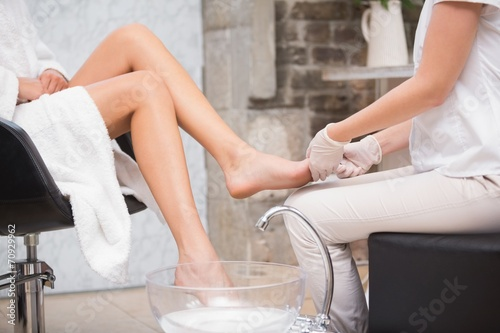 Woman getting a pedicure from beautician