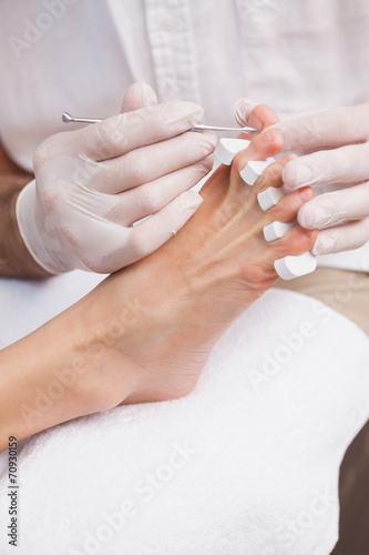 Poster Pedicure Pedicurist cleaning a customers toe nails