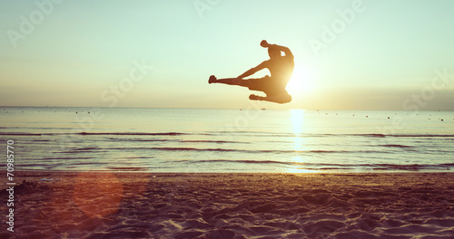 Fotografia  flying kick on the beach