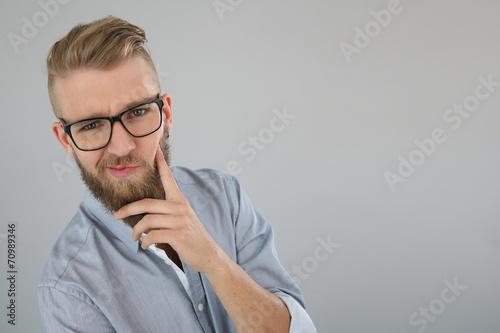 Fotografija  Young man with beard having a doubtful look