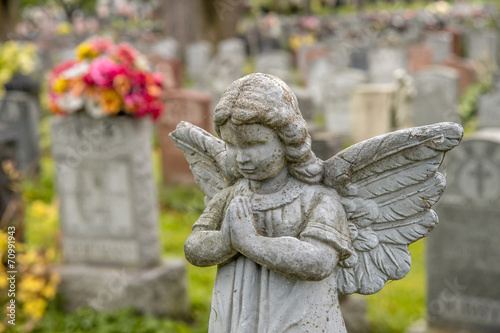 Deurstickers Begraafplaats Praying angel in a cemetary with tombstones in the background