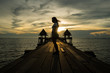 Silhouette of woman standing on old wooden bridge
