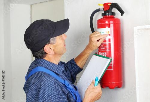 Foto  Fachmann bei der Prüfung Eines Feuerlöschers
