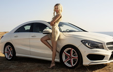 Sexy Woman With Blond Hair Posing Beside A Luxury Auto