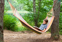 Child Reading Book In Hammock
