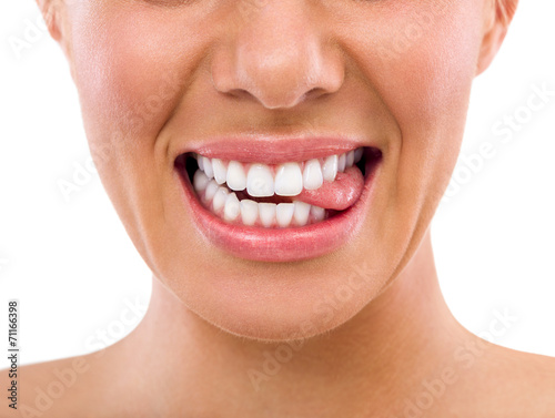 Fotografering  Female biting tongue with perfect teeth
