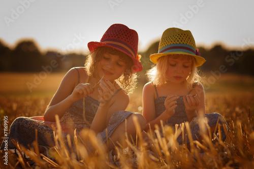 Carta da parati Two girls in a cornfield before sunset