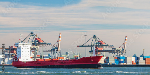 Container ship passing cranes in Rotterdam harbor