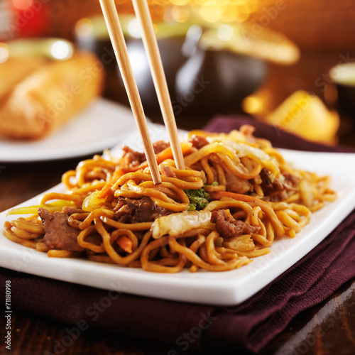 Photo  eating chinese beef lo mein with chopsticks