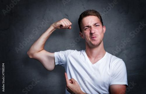 Fotografie, Obraz  Junger mann zeigt auf seinen verkümmerten Arm