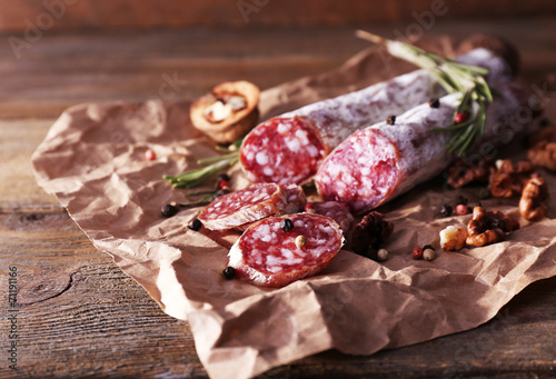 Valokuvatapetti French salami and walnuts on craft paper on wooden background
