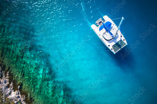 Fototapeta View to catamaran sailing in open sea at windy day. Drone view