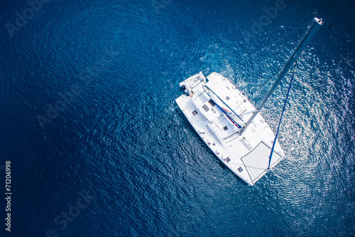 Leinwand Poster View to catamaran sailing in open sea at windy day. Drone view