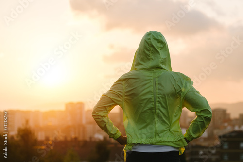 Photo  Athlete looking sunset over city skyline after exercising