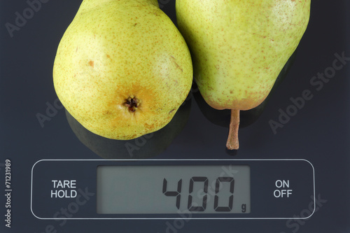 Fotografia  Two green pears on kitchen scale