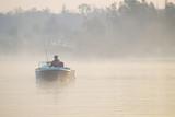 wędkarzna łodzi łowiący ryby o poranku