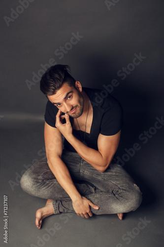 Fotografie, Obraz  Pohledný muž, představující ve studiu na šedém pozadí