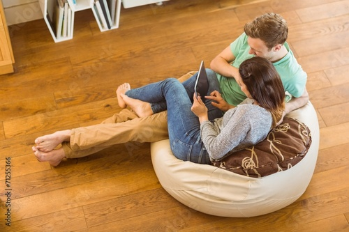 Cute couple using tablet pc on beanbag Wallpaper Mural