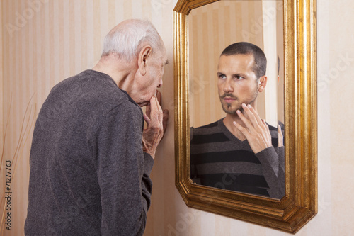 Fotografía  young man looking at an older himself in the mirror