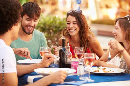 Foto op Canvas Kruidenierswinkel Group Of Young Friends Enjoying Meal In Outdoor Restaurant