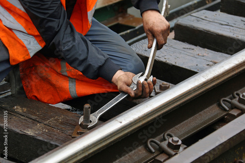 Obraz na płótnie Worker tightens the screw on railroad with two spanners in hands