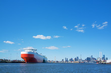Large Cargo Ship In Yarra River With Melbourne CBD Skyline In Th