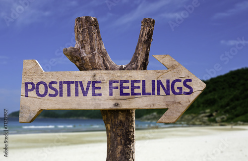 Fotografia  Positive Feelings wooden sign with a beach on background