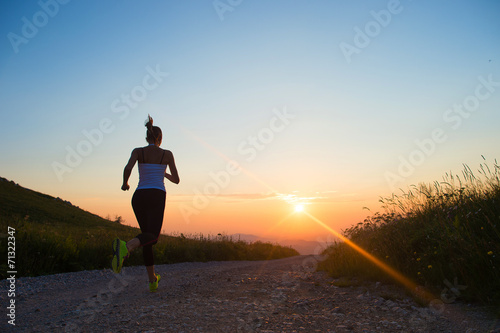In de dag Jogging woman running on a mountain road at summer sunset