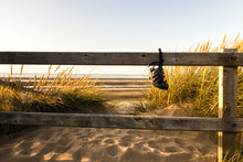 Sandal  Fastened To A Wooden Fence By Its Strap