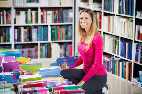 Photographie  Young girl kneeling selecting book in a bookstore