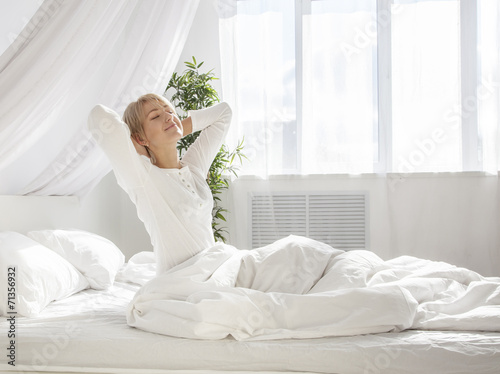 beautiful woman has woken up and is sitting on a white bed