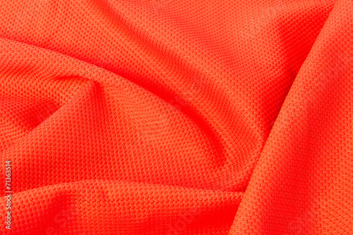 Photo  texture of bright, acid orange cloth with pleats