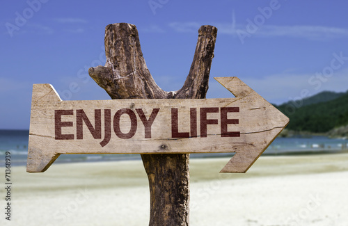 Photo  Enjoy Life wooden sign with a beach on background