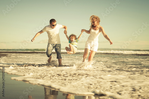 Juliste  Happy family playing on the beach at the day time