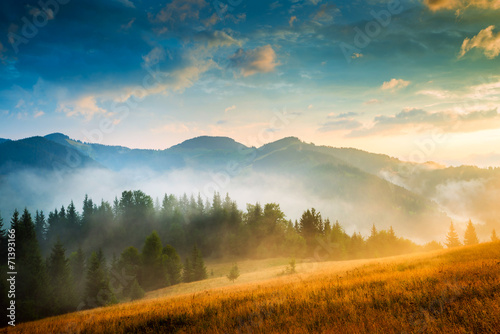 Foto op Canvas Nachtblauw Amazing mountain landscape with fog and a haystack