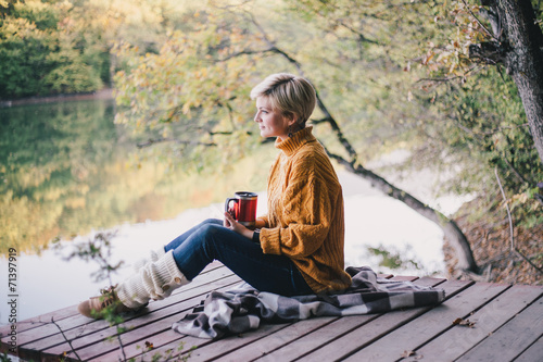 Tuinposter Ontspanning Blond with blue eyes sitting near lake with cup of hot tea