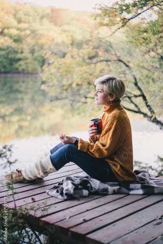 Blond with blue eyes sitting near lake with cup of hot tea