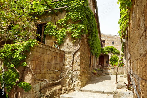 Old small stone medieval street in historical town, Italy