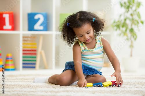 Fototapeta Kid girl playing toys at kindergarten room