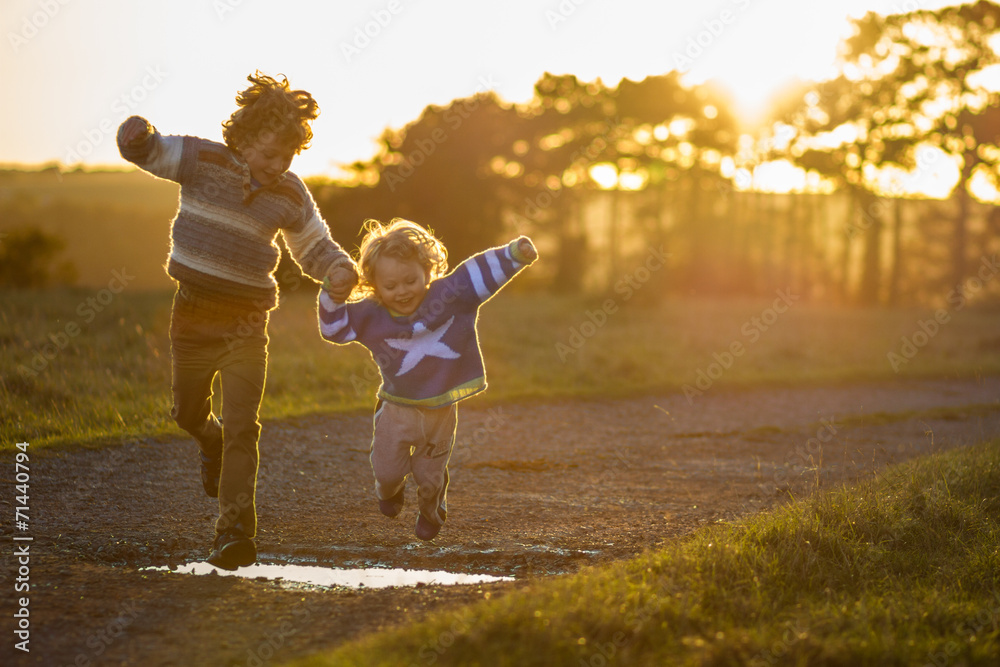 Fototapety, obrazy: two boys jumping over puddles