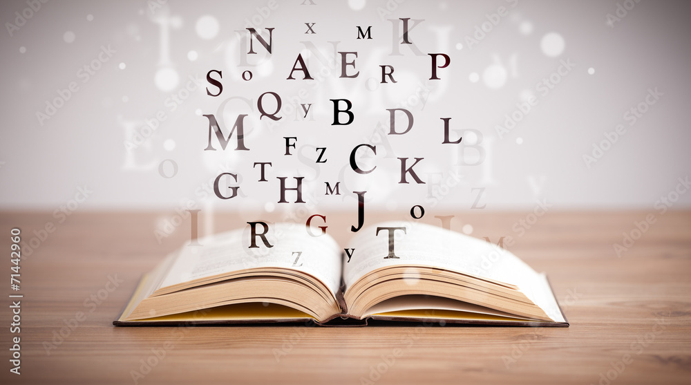 Fototapeta Opened book with flying letters