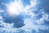 Bright blue sky background with white clouds and shining sun