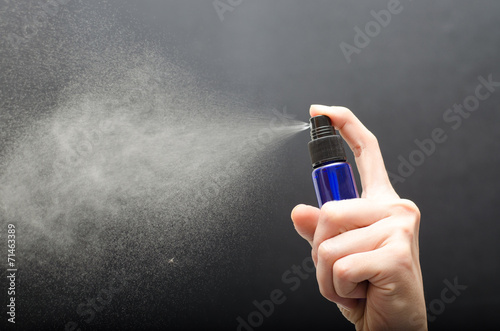 Photo  bottle spraying against gray background