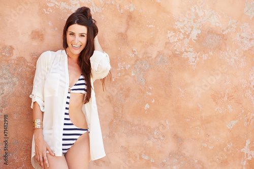 Fotografie, Obraz  Pretty Young Woman Wearing Swimsuit Leaning Against Wall