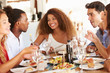 canvas print picture - Group Of Young Friends Enjoying Meal In Outdoor Restaurant