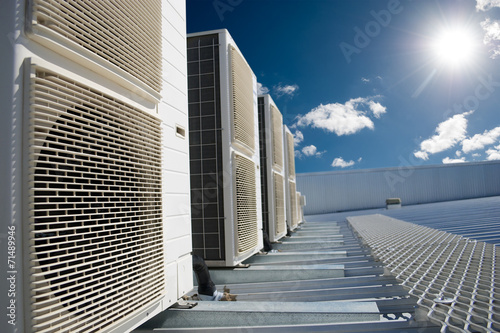 Fotografia, Obraz  Air conditioner units with sun and blue sky