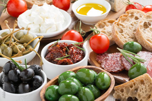 Photo assorted Italian antipasti - olives, salami, pickles and bread