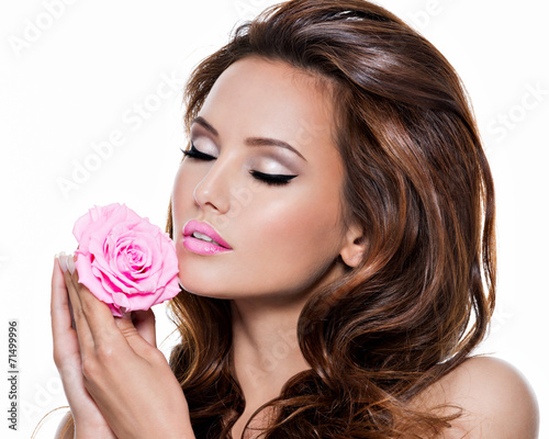 Face of a tender beautiful woman with pink rose flower.