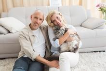 Happy Couple With Pet Cat On Floor